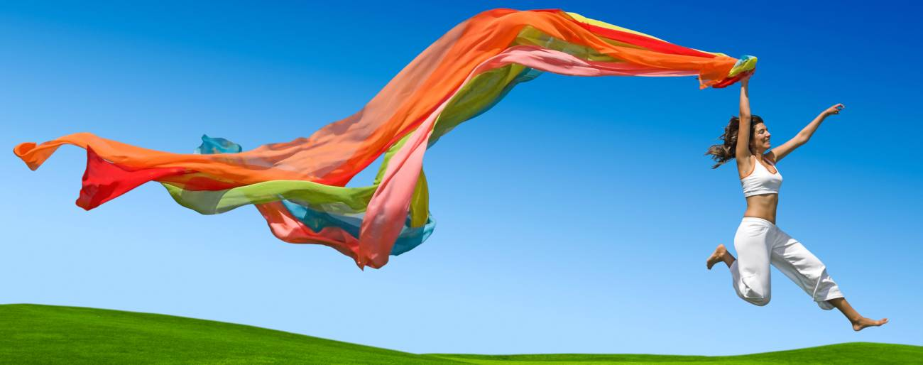 happy woman dancing on green field with rainbow sheet